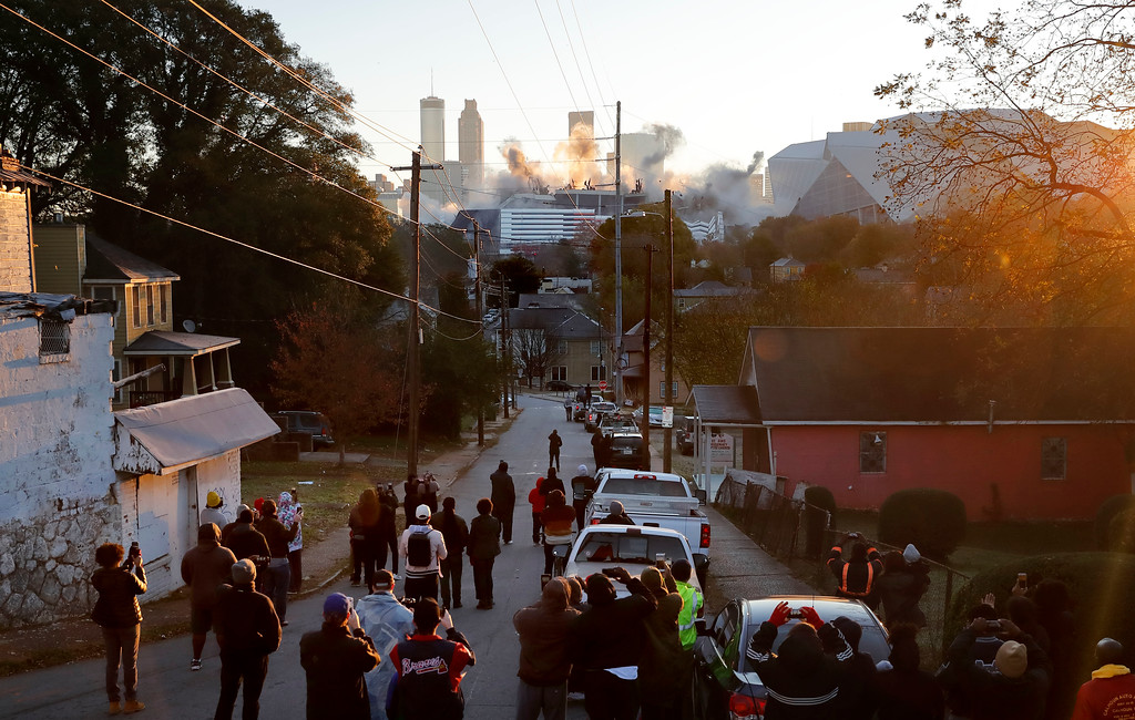 . A crowd watches as the Georgia Dome is imploded as the new Mercedes-Benz Stadium stands to the right in Atlanta, Monday, Nov. 20, 2017. The dome was not only the former home of the Atlanta Falcons but also the site of two Super Bowls, 1996 Olympics Games events and NCAA basketball tournaments among other major events. (AP Photo/David Goldman)