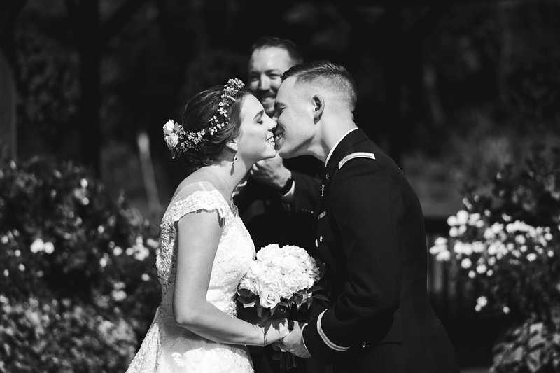 The bride and groom pause for a moment after kissing, smiling, inches from each other.