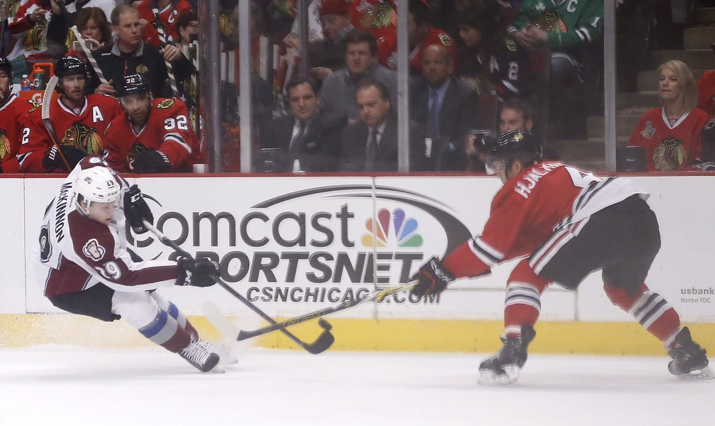 . Colorado Avalanche center Nathan MacKinnon (29) battles Chicago Blackhawks defenseman Niklas Hjalmarsson (4) for a loose puck during the first period of an NHL hockey game Tuesday, Jan. 6, 2015, in Chicago. (AP Photo/Charles Rex Arbogast)