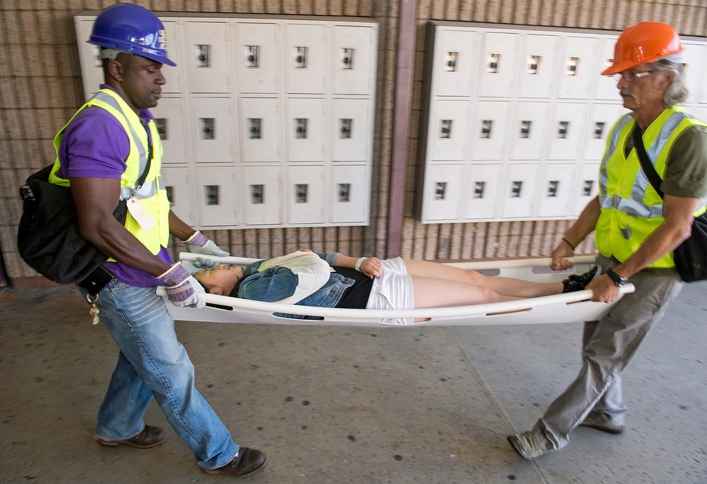 ". Diamond Bar High staff members Noel Foly, left, and David Hamel carry an ""injured\"" student to triage during the Great ShakeOut earthquake drill at the Diamond Bar campus October 17, 2013.  (Staff photo by Leo Jarzomb/SGV Tribune)"
