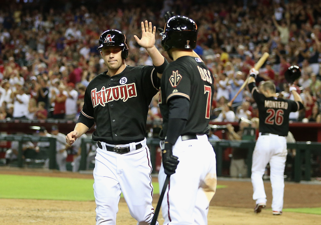 . PHOENIX, AZ - JULY 05:  Aaron Hill #2 of the Arizona Diamondbacks high fives Cody Ross #7 after scoring against the Colorado Rockies during the sixth inning of the MLB game at Chase Field on July 5, 2013 in Phoenix, Arizona.  (Photo by Christian Petersen/Getty Images)