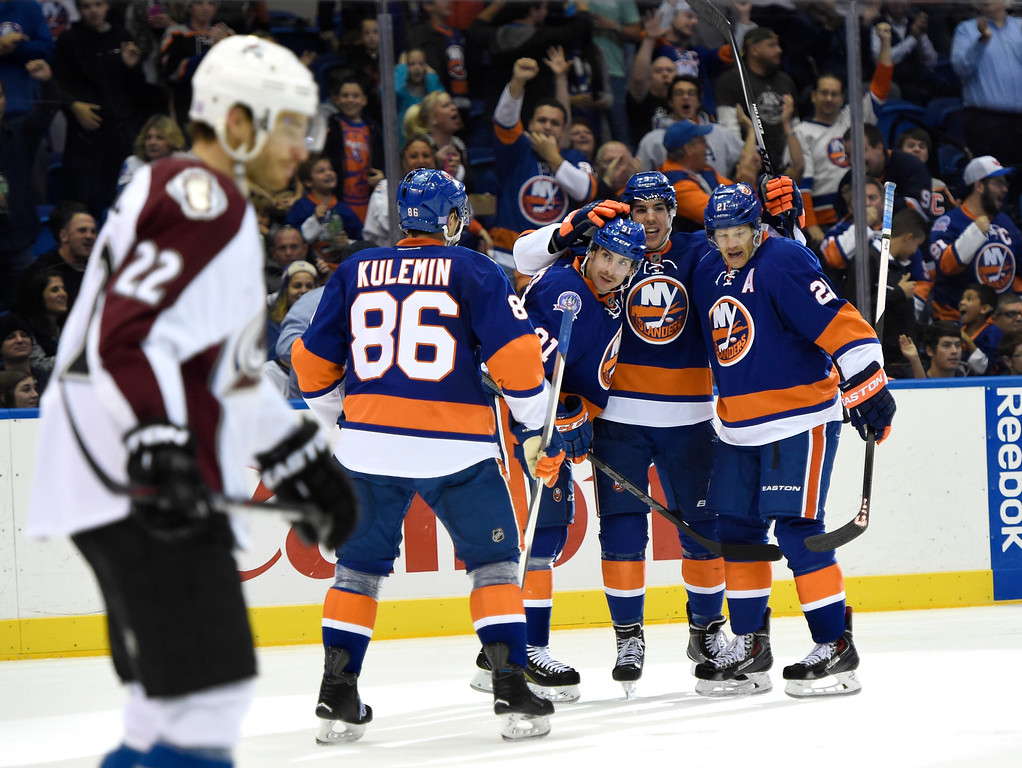 . New York Islanders defenseman Travis Hamonic (3) celebrates his goal with  center John Tavares (91), Kyle Okposo (21) and left wing Nikolai Kulemin (86) as Colorado Avalanche defenseman Zach Redmond (22) reacts in the second period of an NHL hockey game at Nassau Coliseum on Tuesday, Nov. 11, 2014, in Uniondale, N.Y. (AP Photo/Kathy Kmonicek)