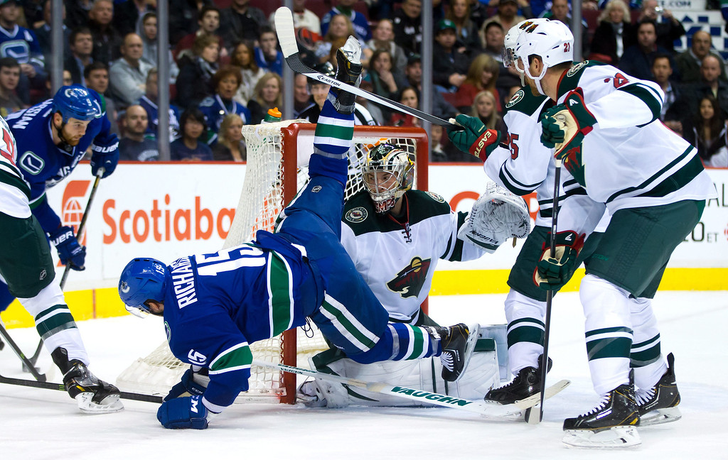 . Vancouver Canucks\' Brad Richardson, left, is tripped up by Minnesota Wild\'s Jonas Brodin, back right, of Sweden, in front of Wild goalie Darcy Kuemper as Wild\'s Kyle Brodziak, right, watches during the first period of an NHL hockey game Friday, Feb. 28, 2014, in Vancouver, British Columbia. (AP Photo/The Canadian Press, Darryl Dyck)