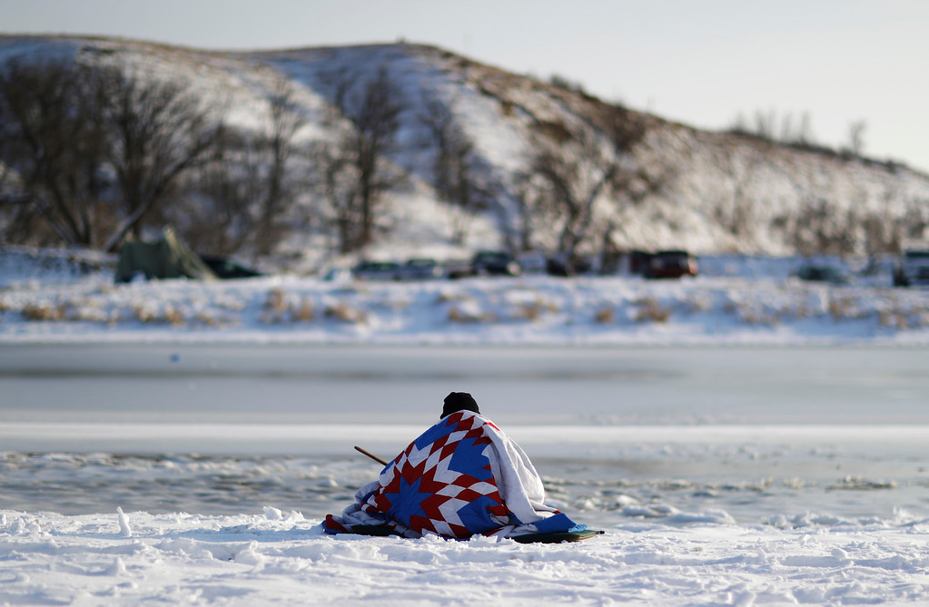 . A man sits along the Cannonball river at the Oceti Sakowin camp where people have gathered to protest the Dakota Access oil pipeline in Cannon Ball, N.D., Saturday, Dec. 3, 2016. (AP Photo/David Goldman)