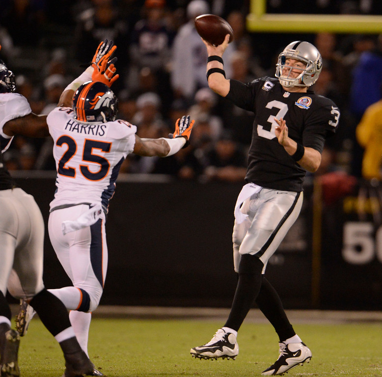 . Oakland Raiders quarterback Carson Palmer (3) is rushed on his throw by Denver Broncos cornerback Chris Harris (25) during the third quarter Thursday, December 6, 2012 during Thursday Night Football at O.c Coliseum in Oakland  John Leyba, The Denver Post