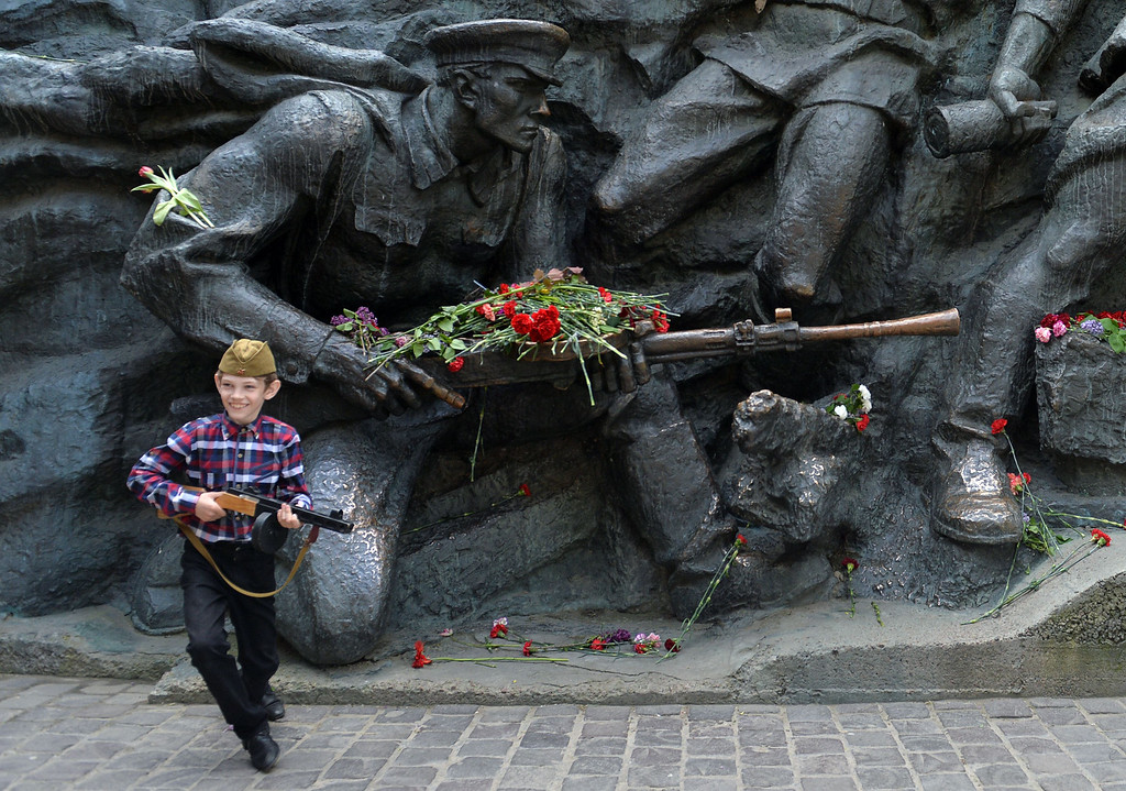 . A boy walks in front of a WWII monument during a ceremony marking the Victory Day in the Ukrainian capital of Kiev on May 9, 2014. Ukraine\'s government on Friday protested Russian President Vladimir Putin\'s visit to annexed Crimea, where he inspected Russian naval forces in a commemoration of the Soviet victory in World War II.   AFP PHOTO/ SERGEI SUPINSKY/AFP/Getty Images