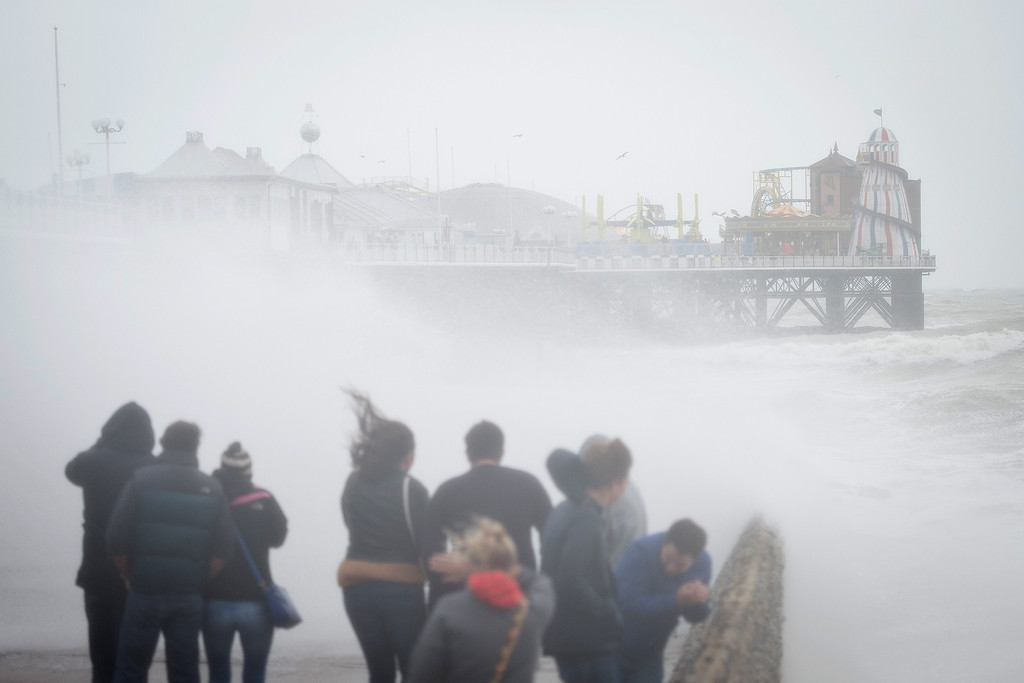 . People watch as large waves crash against the walls of Brighton seafront, in southern England on October 27, 2013 as a predicted storm starts to build. Britain was braced on October 27 for its worst storm in a decade, with heavy rain and winds of more than 80 miles (130 kilometres) an hour set to batter the south of the country.  LEON NEAL/AFP/Getty Images