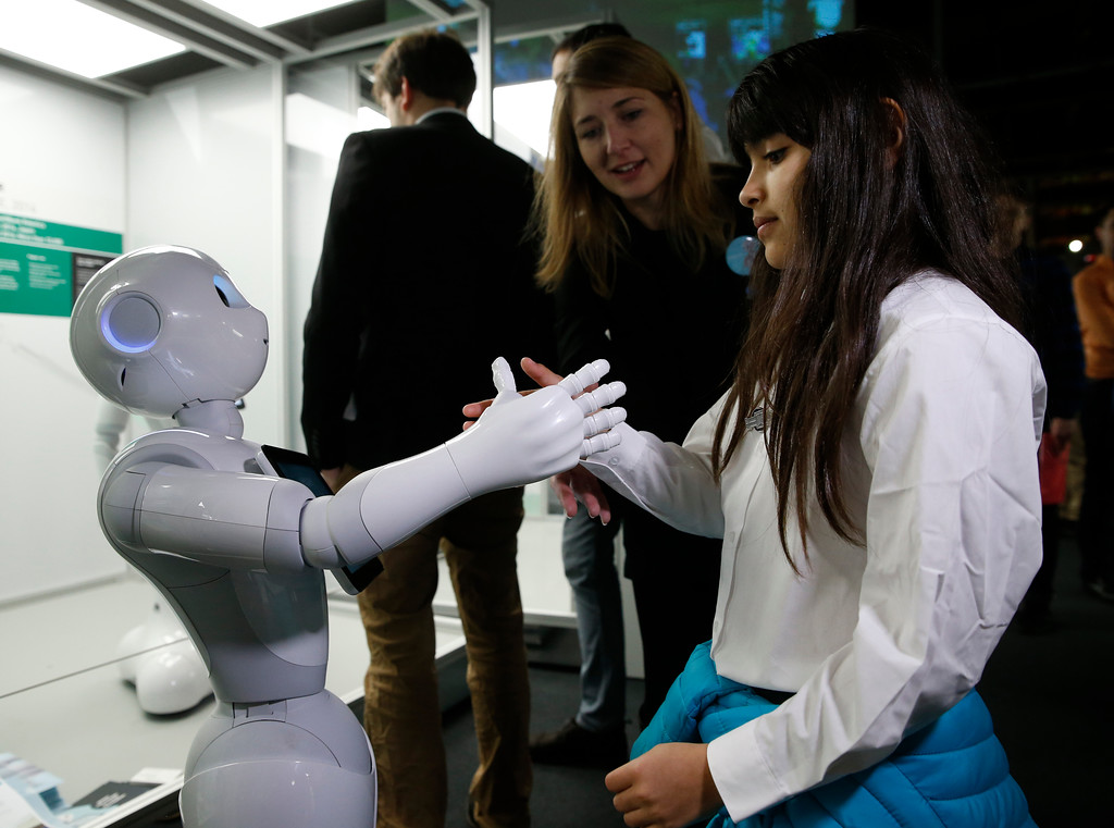 . Charllotte Abbot shakes hands with Pepper an interactive French-Japanese robot, during a press preview for the Robots exhibition held at the Science Museum in London, Tuesday, Feb. 7, 2017. The exhibition which shows 500 years of mechanical and robotic advances is open to the public form Feb. 8 through to Sept. 3. (AP Photo/Alastair Grant)