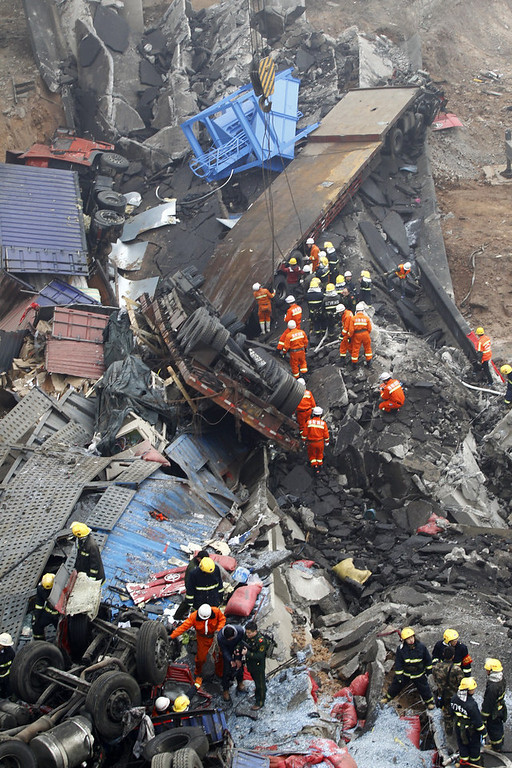. Rescuers work under the collapsed Yichang bridge near the city of Sanmenxia, central China\'s Henan province, on February 1, 2013. A fireworks-laden truck exploded as it crossed a bridge in central China on Friday, killing 26 people as the structure collapsed and vehicles plummeted to the ground, state-run media reported. An 80-metre long part of the bridge collapsed and six vehicles had been retrieved from the debris, China\'s official news agency Xinhua said. The bridge near the city of Sanmenxia is on the G30 expressway, the longest road in China, which stretches for nearly 4,400 kilometers (2,700 miles) from China\'s western border with Kazakhstan to the eastern Yellow Sea.      AFP PHOTO  STR/AFP/Getty Images