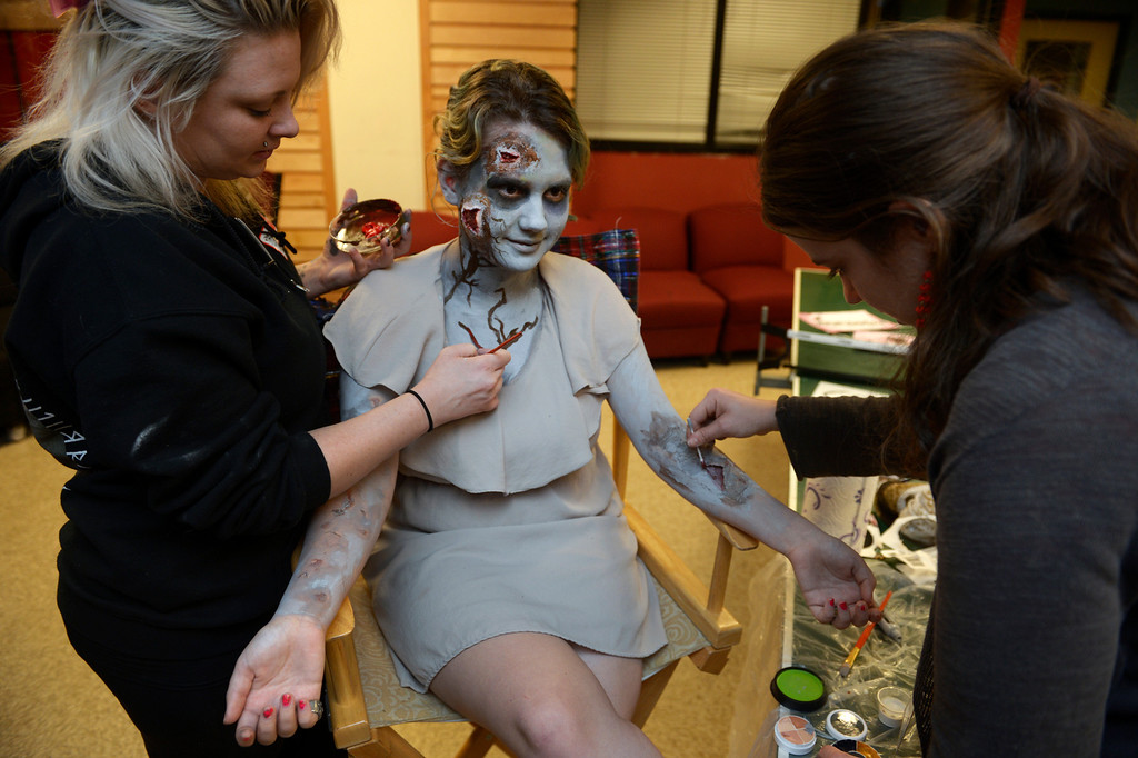 """. BOULDER, CO- FEBRUARY 19:  Danica Minor, left, and Kristy Pike, right, both  make-up artists with Theatrical Costumes Etc, apply \""""Zombie\"""" make up to zombie Phillipa Keosheyan 14. With the help of a professional videographer, Fairview High School students produced a zombie video to advertise an Awareness Drive in Boulder Valley schools designed to bring attention to a variety of mental health and wellness issues.  Students were made to look like zombies by make-up artists from Theatrical Costumes, Etc. (Photo By Helen H. Richardson/ The Denver Post)"""
