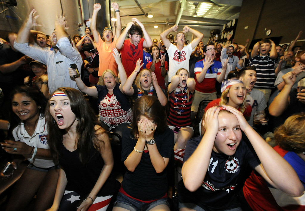 . Leah Honkanen, Elizabeth Keller and Elizabeth Earles, of Huntsville, cheer with fans who showed up at Straight to Ale Brewery to watch the U.S. play Belgium in a World Cup soccer match Tuesday, July 1, 2014, in Huntsville, Ala. (AP Photo/AL.com, Eric Schultz)