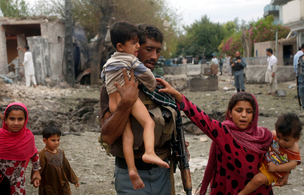 . An Afghan policeman carries a boy as he helps local residents move away from the site of a suicide attack at the Indian consulate in Jalalabad province August 3, 2013. A suicide bomber attacked the Indian consulate in the eastern Afghan capital of Jalalabad on Saturday, Indian officials and local police said, killing six people and wounding 22. REUTERS/Parwiz