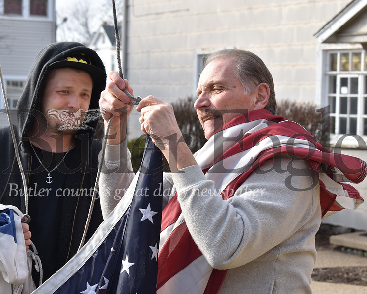 In last week's storm, the wind tangled up the American and Christian flags and broke the brackets that held up the flags which reside on the flagpole outside North Street Christian Church at 226 W. North Street in Butler. On Thursday afternoon, Bob Seaver, right, an administrator at the church and Jeremy Melnick, a maintenance technician at the church, took advantage of the nice but chilly weather to attempt reattaching the flags. The American flag is back flying on the pole, but the bracket's for the Christian flag, which Melnick is holding, will be put up at a later date.Photos by Lauryn Halahurich/Butler Eagle