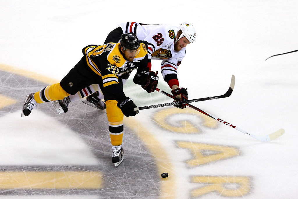 . Daniel Paille #20 of the Boston Bruins skates for the puck against Bryan Bickell #29 of the Chicago Blackhawks in Game Six of the 2013 NHL Stanley Cup Final at TD Garden on June 24, 2013 in Boston, Massachusetts.  (Photo by Elsa/Getty Images)