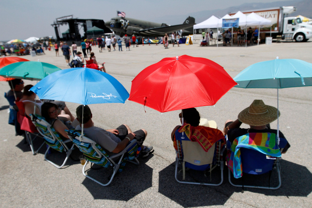 . AirFest attendees relax under umbrellas during the Hangar 24 AirFest and 6th Anniversary Celebration on Saturday, May 17, 2014 at the Redlands Municipal Airport in Redlands, Ca. (Photo by Micah Escamilla/Redlands Daily Facts)
