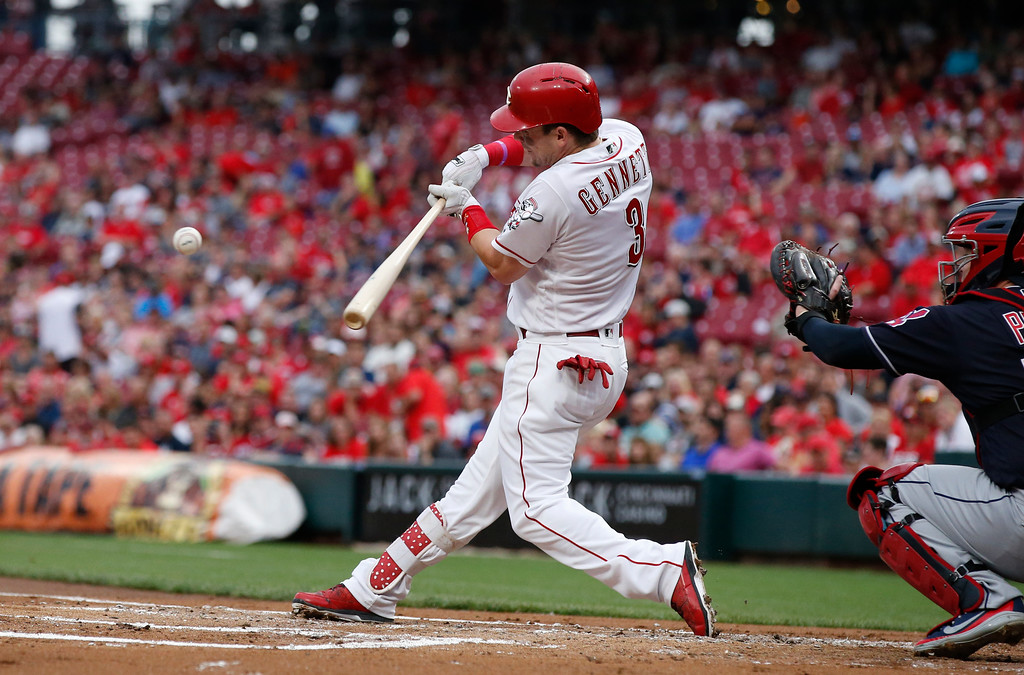 . Cincinnati Reds\' Scooter Gennett hits an RBI single off Cleveland Indians starting pitcher Shane Bieber during the first inning of a baseball game Wednesday, Aug. 15, 2018, in Cincinnati. (AP Photo/Gary Landers)