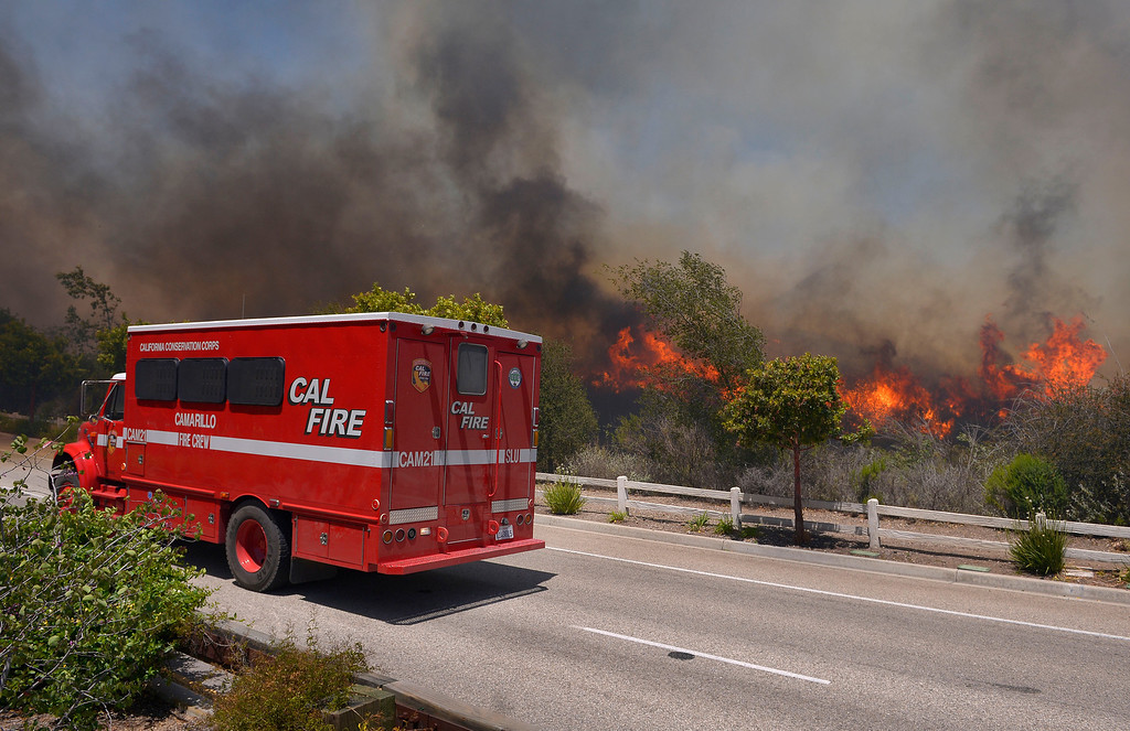 . A fire vehicle stands by as a wildfire burns along a roadside in Thousand Oaks, Calif., Thursday, May 2, 2013.  (AP Photo/Mark J. Terrill)
