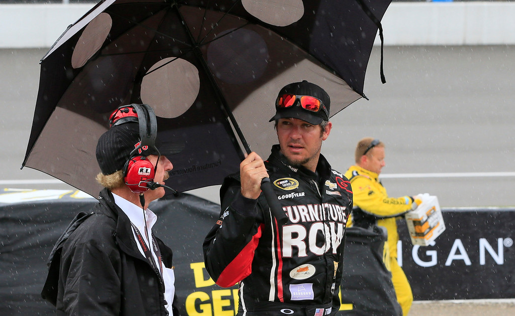 . Martin Truex Jr., waits out a rain delay during the NASCAR Sprint Cup series auto race at Michigan International Speedway, Sunday, June 14, 2015, in Brooklyn, Mich. (AP Photo/Carlos Osorio)