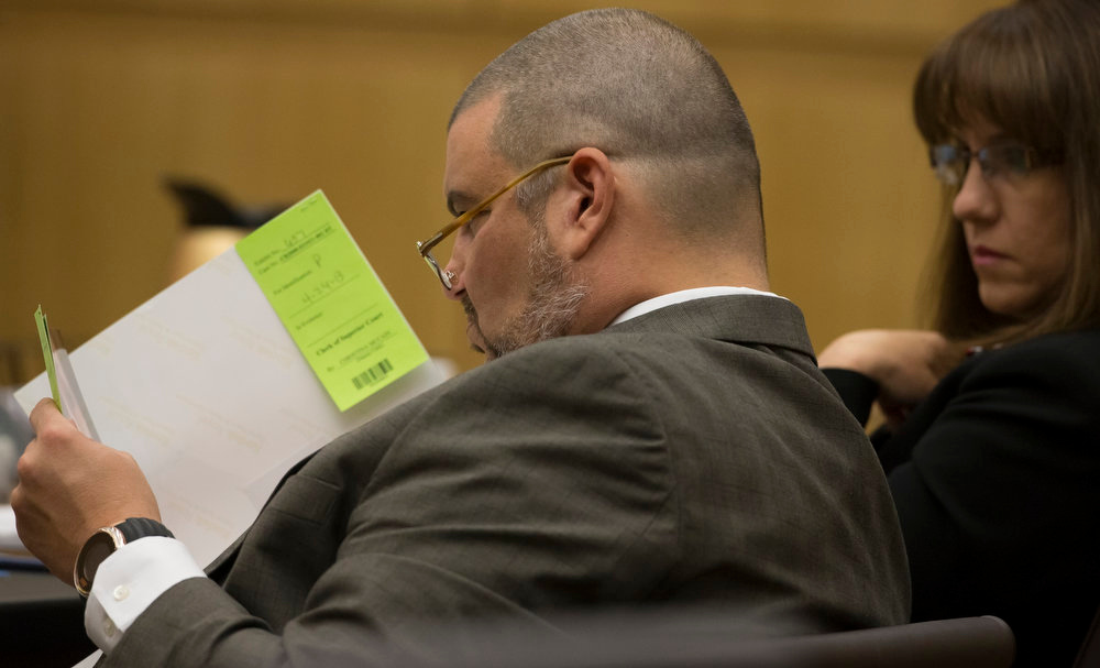 . Defense attorney Kirk Nurmi, left, looks at photos during the Jodi Arias murder trial on Wednesday, April 24, 2013. Arias faces a potential death sentence if convicted of first-degree murder in the June 2008 killing of her one-time boyfriend at his suburban Phoenix home. Authorities say she planned the attack on Travis Alexander in a jealous rage. Looking on is defense attorney Jennifer Wilmott. (AP Photo/The Arizona Republic, Mark Henle, Pool)