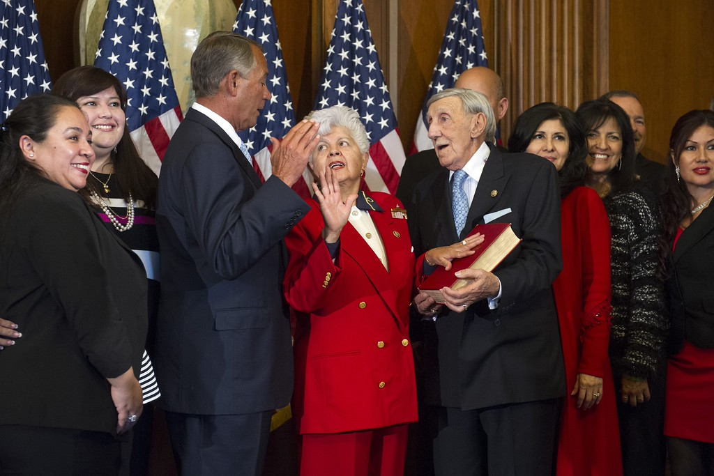 . House Speaker John Boehner of Ohio administers a ceremonial re-enactment of the House oath-of-office to Rep. Grace Napolitano, D-Calif., accompanied by her husband Frank and family, Tuesday, Jan. 6, 2015, on Congress Hill in Washington. (AP Photo/Cliff Owen)
