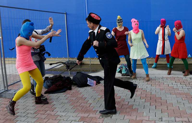 . A Cossack militiaman attacks Nadezhda Tolokonnikova and a photographer as she and fellow members of the punk group Pussy Riot, including Maria Alekhina, center, in the pink balaclava, stage a protest performance in Sochi, Russia, on Wednesday, Feb. 19, 2014. The group had gathered in a downtown Sochi restaurant, about 30km (21miles) from where the Winter Olympics are being held. They ran out of the restaurant wearing brightly colored clothes and ski masks and were set upon by about a dozen Cossacks, who are used by police authorities in Russia to patrol the streets. (AP Photo/Morry Gash)