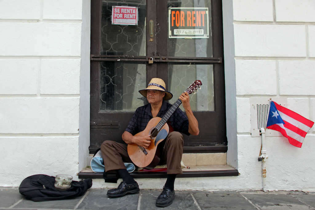 . A man plays his guitar while he begs for money in front of a closed down business in Old San Juan, Puerto Rico, Monday, June 29, 2015. International economists released a critical report on Puerto Rico\'s economy Monday on the heels of the governor\'s warning that the island can\'t pay its $72 billion public debt. (AP Photo/Ricardo Arduengo)
