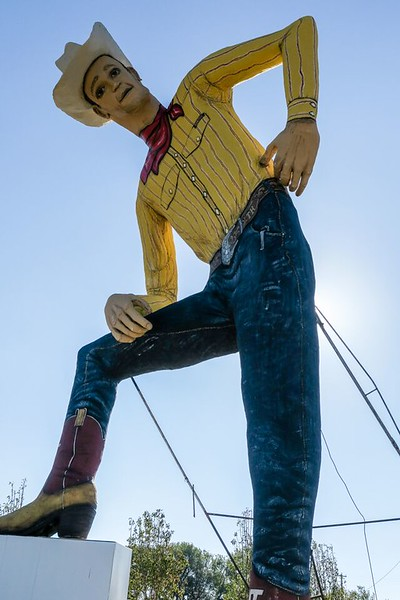 Statue of a big cowboy with yellow shirt and blue jeans