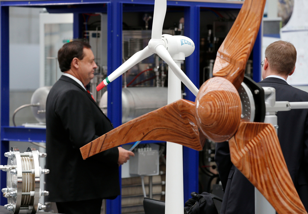 Description of . Visitors stand next to models of wind turbines at the booth of C.R.I.E.L at the Hanover Messe on the first day of the industrial trade fair, in Hanover April 8, 2013. The Hanover fair runs from April 8 -12. REUTERS/Fabrizio Bensch