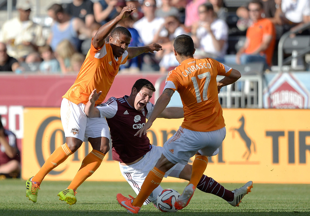 . Colorado Rapids midfielder Dillon Powers (8) gets a shove from behind by Houston Dynamo defender Jermaine Taylor (4) as Houston Dynamo midfielder Servando Carrasco (17) comes in for the ball during the first half June 1, 2014 at Dick\'s Sporting Goods Park. (Photo by John Leyba/The Denver Post)