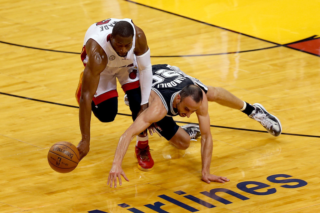 . Dwyane Wade #3 of the Miami Heat and Manu Ginobili #20 of the San Antonio Spurs go after a loose ball in the first half during Game Two of the 2013 NBA Finals at AmericanAirlines Arena on June 9, 2013 in Miami, Florida.   (Photo by Mike Ehrmann/Getty Images)