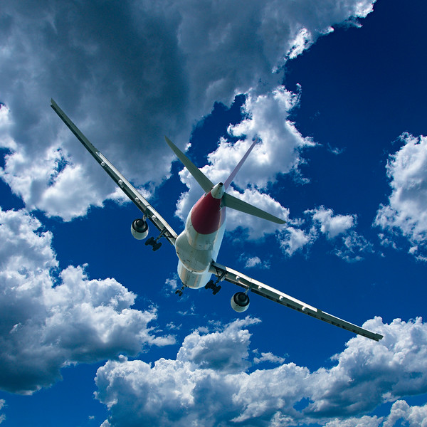 Aircraft in flight with cumulus cloud in blue sky. Australia.