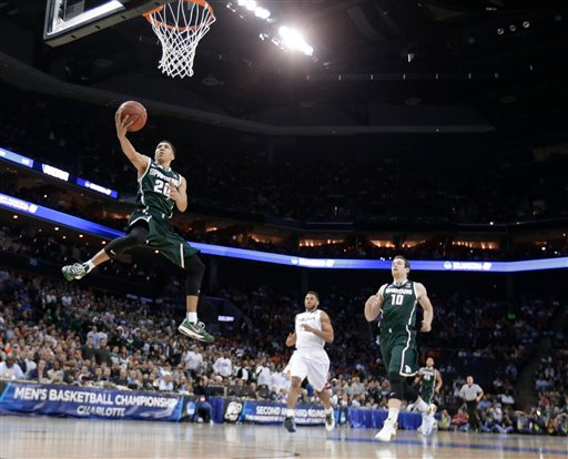 . Michigan State\'s Travis Trice (20) drives to the basket against Virginia during the first half of an NCAA tournament college basketball game in the Round of 32 in Charlotte, N.C., Sunday, March 22, 2015. (AP Photo/Gerald Herbert)