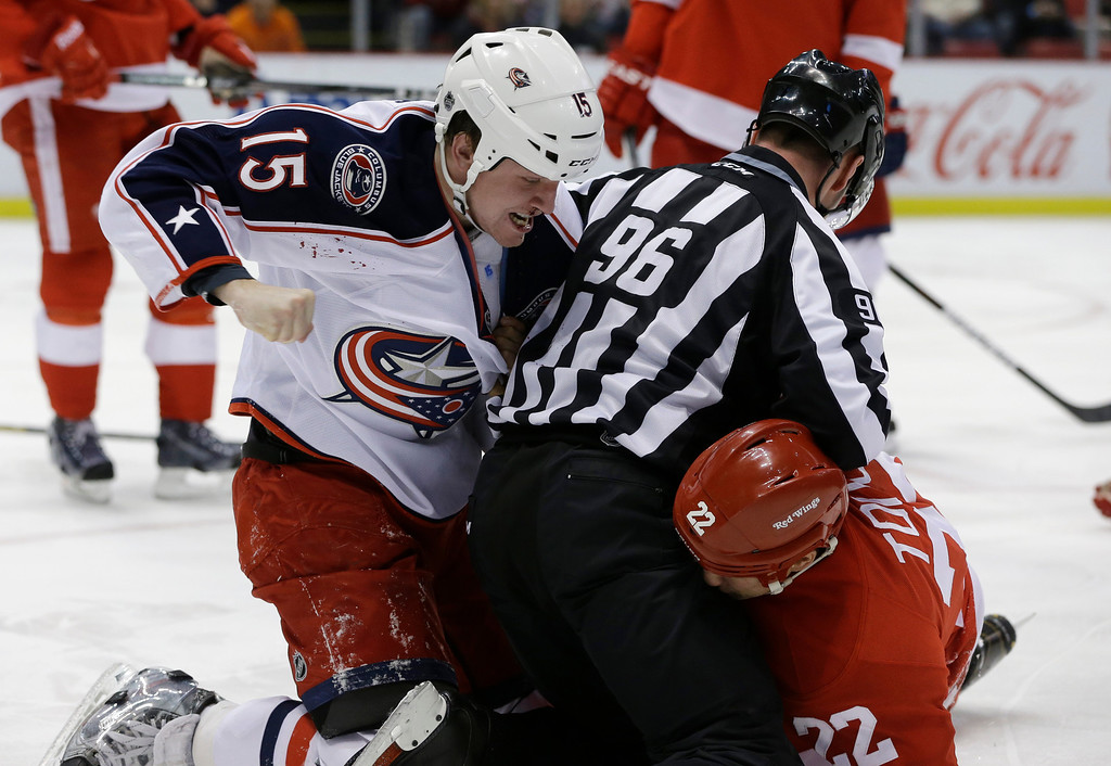 . Linesman David Brisebois (96) separates Columbus Blue Jackets right wing Derek Dorsett (15) and Detroit Red Wings right wing Jordin Tootoo (22) during the first period of an NHL hockey game in Detroit, Thursday, Feb. 21, 2013. (AP Photo/Carlos Osorio)