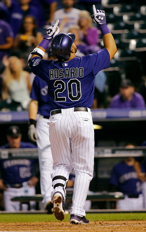 . Colorado Rockies\' Wilin Rosario celebrates a solo home run as he crosses home plate to during the first inning of a baseball game against the Los Angeles Dodgers Monday, Sept. 15, 2014, in Denver. (AP Photo/Jack Dempsey)
