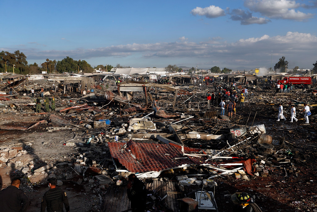 . Firefighters and rescue workers walk through the scorched ground of the open-air San Pablito fireworks market, in Tultepec, outskirts of Mexico City, Mexico, Tuesday, Dec. 20, 2016.  An explosion ripped through Mexico�s best-known fireworks market on the northern outskirts of the capital Tuesday, injuring scores and killing dozens, according to Mexican Federal Police. (AP Photo/Eduardo Verdugo)