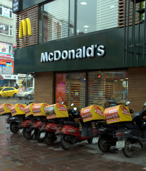 Fleet of delivery scooters at a McDonalds.