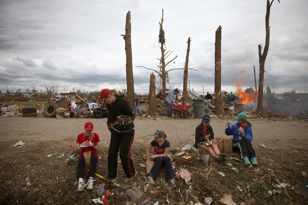 . Volunteers (L-R), Rachel Dawson, Courtney Dawson, Anna Dawson, Sarah Grace Knave and Wanda Knave take a break from cleaning up tornado debris, April 30, 2014 in Vilonia, Arkansas. Deadly tornadoes ripped through the region starting on April 27 leaving more than two dozen dead. The storm system has also brought severe flooding to Florida\'s Panhandle.  (Photo by Mark Wilson/Getty Images)