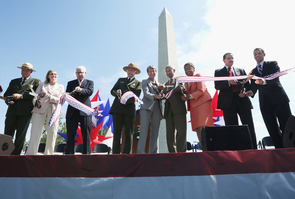 . (L-2nd R) National Mall and Memorial Parks Superintendent Robert Vogel, President of Trust for the National Mall Caroline Cunningham, Co-Founder and Co-CEO of The Carlyle Group David Rubenstein, National Park Service Director Jonathan Jarvis, U.S. Interior Secretary Sally Jewell, Counselor to President Obama John Podesta, Rep. Eleanor Holmes Norton (D-DC), and DC Mayor Vincent Gray participate in a ribbon cutting during a reopening ceremony for the Washington Monument May 12, 2014 in Washington, DC.   (Photo by Alex Wong/Getty Images)