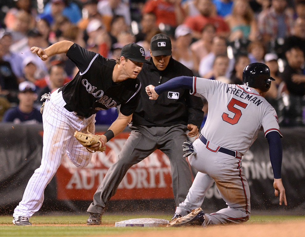 . Atlanta baserunner Freddie Freeman stole third base and scored when Rockies catcher Wilin Rosario threw out of the reach of infielder DJ LeMahieu in the sixth inning. The Colorado Rockies hosted the Atlanta Braves Tuesday night, June 10, 2014. (Photo by Karl Gehring/The Denver Post)