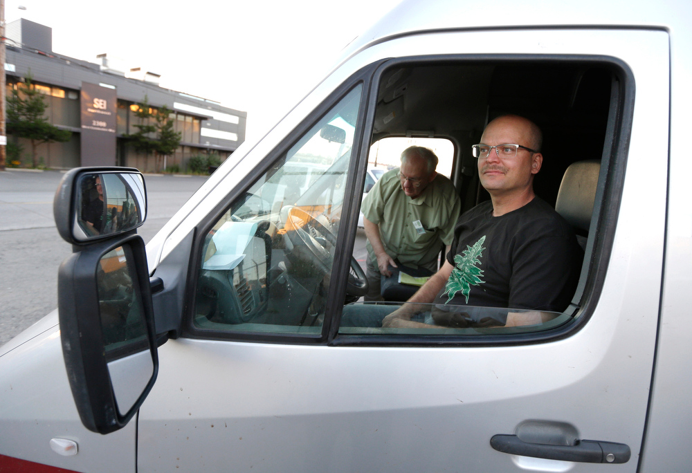 . In this July 8, 2014, photo, Phil Tobias, right, director of Sea of Green Farms, prepares to drive a delivery van in Seattle with farm owner Bob Leeds, left, as they set out on their first delivery of recreational marijuana to a store in Bellingham, Wash. It was the first delivery for the company since retail licenses were issued by the state on Monday, July 7. (AP Photo/Ted S. Warren)