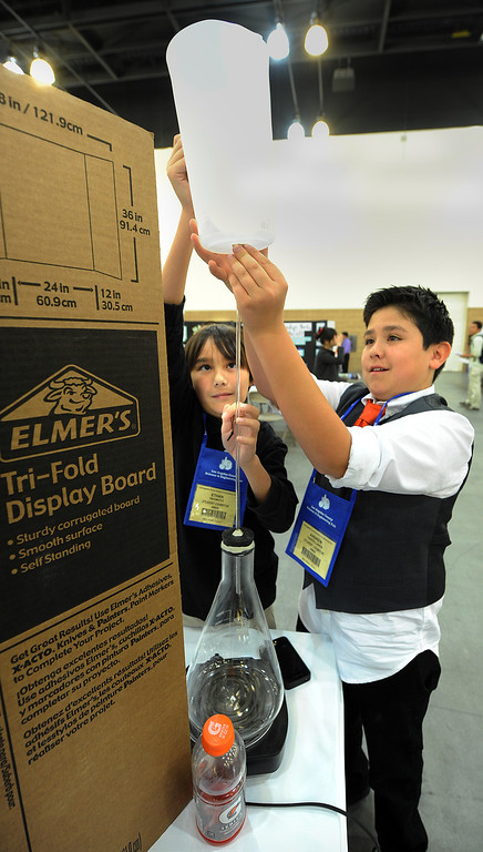 ". Ethan Okamoto, left and Andrew Castellanos in the Junior Division Earth/Space Sciences placing a pitcher on top of their experiment demonstrating their science project, ""How Do Geysers Erupt\"",  at the 63rd annual Los Angeles County Science Fair at Pasadena Convention Center Friday, March 22, 2013. Organizers scrambled to raise enough funds this year, and almost had to do without tables and chairs until a $25,000 donation by Southern California Edison at the last minute. (SGVN/Photo by Walt Mancini/SXCity)"