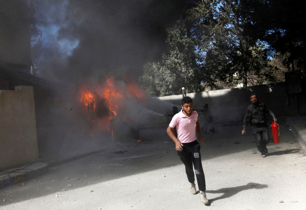 . A man runs as smoke rises from buildings damaged by what activists said were shelling by forces loyal to President Bashar al-Assad in Raqqa province, eastern Syria, March 14, 2013. REUTERS/Hamid Khatib