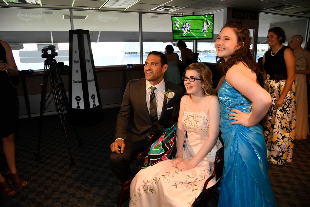 . Denver Broncos quarterback Mark Sanchez takes a photo with Ansley Odom, 15, (M) and Ayla Charness, 15, during a Night of Champions prom. Teens got their makeup, hair and nails done before prom night May 13, 2016 at Sports Authority Field at Mile High. Some of the teens missed their own prom due to illness and just couldn\'t attend. Childrens Hospital hosted the Night of Champions gala. (Photo By John Leyba/The Denver Post)