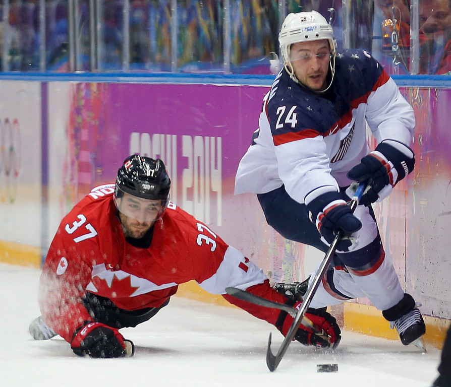 . Canada forward Patrice Bergeron USA forward Ryan Callahan vie for the puck during the first period of a men\'s semifinal ice hockey game at the 2014 Winter Olympics, Friday, Feb. 21, 2014, in Sochi, Russia. (AP Photo/Julio Cortez)