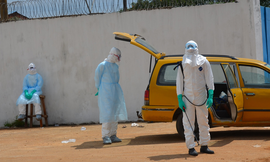 ". Health workers wearing protective suits await on September 23, 2014 outside  the ""Island Clinic\"", a new Ebola treatment centre that opened in Monrovia. The first members of a team of 165 Cuban doctors and health workers have arrived in Sierra Leone to help the fight against Ebola, a health official said Tuesday.  ZOOM DOSSO/AFP/Getty Images"