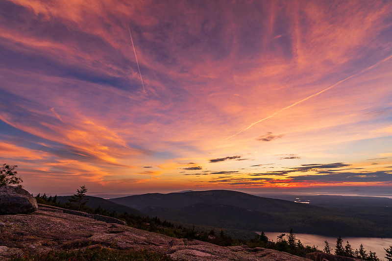 """Viewing the sunset from Cadillac Mountain summit never gets old. I always find myself among dozens of people scattered among the pink granite and boulders eagerly waiting for the fiery show. But as predicted, most people immediately get up and leave once the sun sets below the horizon. Maybe they don't understand that it's the next half hour that the most vibrant of colors are displayed, especially on patchy days like this.<br /> <br /> """"Sunsets, like childhood, are viewed with wonder not just because they are beautiful but because they are fleeting."""" - Richard Paul Evans"""