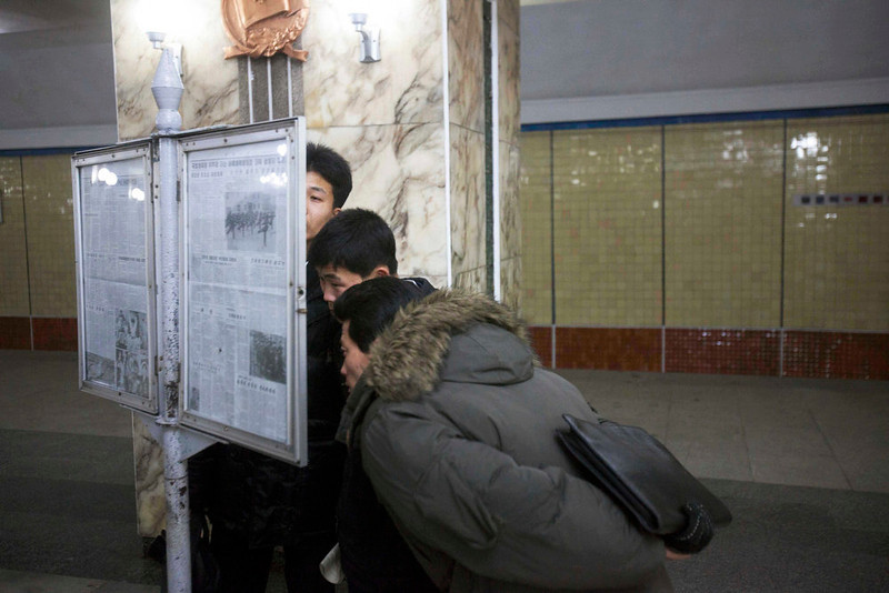 . Men read a newspaper on public display inside a subway station in Pyongyang, North Korea on March 10, 2011. (AP Photo/David Guttenfelder)