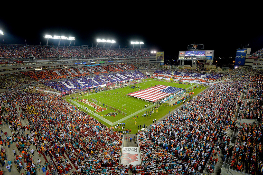 . An overall inside view of Raymond James Stadium as fans honor military and veterans before an NFL game between the Miami Dolphins and the Tampa Bay Buccaneers, Monday, November 11, 2013 in Tampa, Fla.  50,000 cards were provided to fans by USAA, the official military appreciation sponsor of the NFL. (Scott Miller/AP Images for USAA)