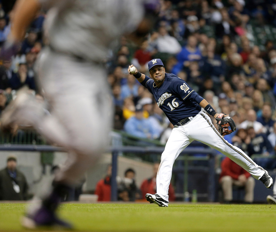. Milwaukee Brewers\' Aramis Ramirez (16) can\'t throw out Colorado Rockies\' Michael Cuddyer, left, during the seventh inning of a baseball game Tuesday, April 2, 2013, in Milwaukee. (AP Photo/Jeffrey Phelps)