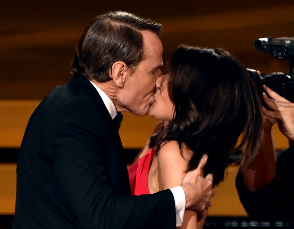 . Actress Julia Louis-Dreyfus (R) wins Outstanding Lead Actress in a Comedy Series for \'Veep\' and kisses actor Bryan Cranston (L) onstage at the 66th Annual Primetime Emmy Awards held at Nokia Theatre L.A. Live on August 25, 2014 in Los Angeles, California.  (Photo by Kevin Winter/Getty Images)